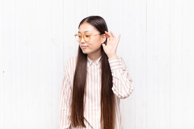 Asiatische junge frau, die ernst und neugierig aussieht, zuhört, versucht, ein geheimes gespräch oder klatsch zu hören, lauscht