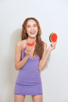Asiatische junge frau, die frische wassermelone lokalisiert auf einem weiß isst. glückliche frau mit obst.