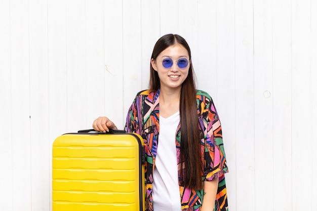 Asiatische junge frau, die fröhlich und beiläufig mit einem positiven, glücklichen, selbstbewussten und entspannten ausdruck lächelt. urlaubskonzept