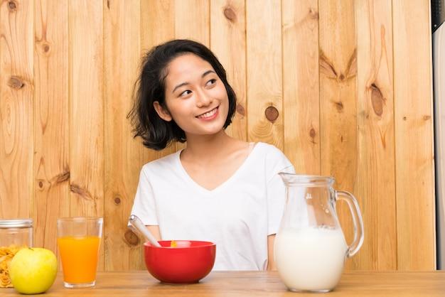 Asiatische junge frau, die frühstücksmilch hat, oben zu lachen und zu schauen