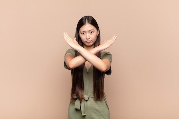Asiatische junge frau, die genervt und krank von ihrer haltung aussieht und genug sagt! die hände waren vorne gekreuzt und sagten dir, du sollst aufhören