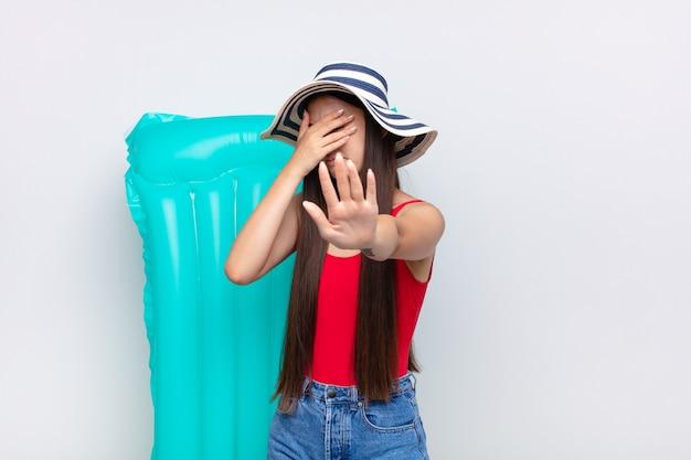 Asiatische junge frau, die gesicht mit hand bedeckt und andere hand lokalisiert aufstellt