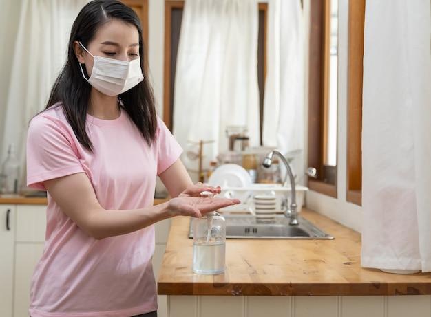 Asiatische junge frau, die gesichtsmaske oder schutzmaske trägt, die zu hause arbeitet und ihre hände mit desinfektionsgel während des ausbruchs von coronavirus oder covid 19 reinigt.