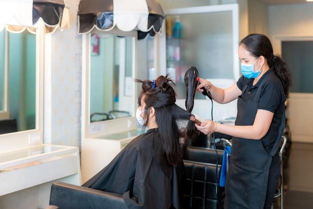 Asiatische junge frau, die gesichtsmasken trägt, um sich während des friseurs mit fön vor covid-19 zu schützen, und fön zu schwarzem haar im schönheitssalon.
