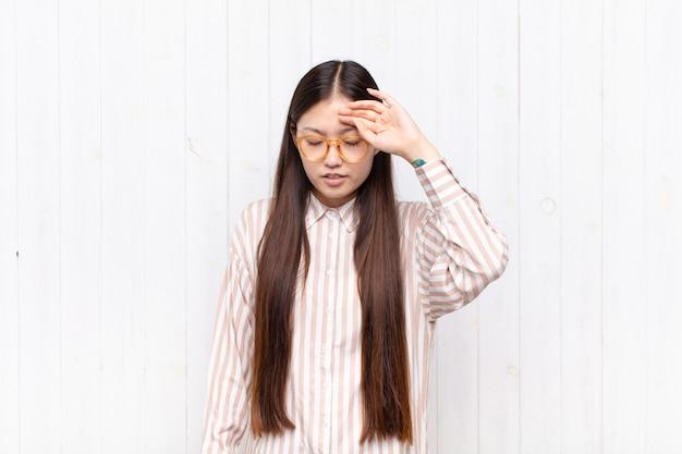 Asiatische junge frau, die gestresst, müde und frustriert aussieht, schweiß von der stirn trocknet, sich hoffnungslos und erschöpft fühlt