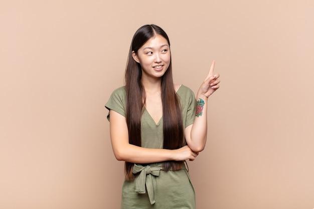 Asiatische junge frau, die glücklich lächelt und seitlich isoliert schaut
