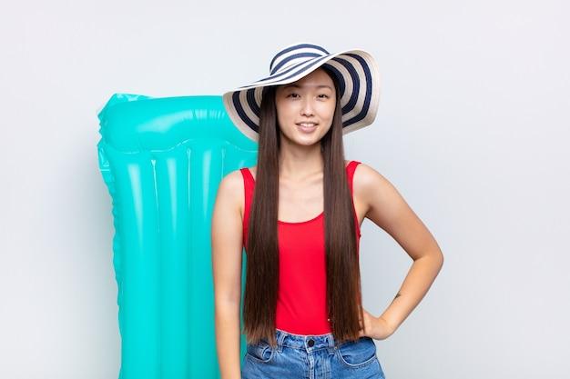 Asiatische junge frau, die glücklich mit einer hand auf hüfte lächelt und zuversichtlich isoliert