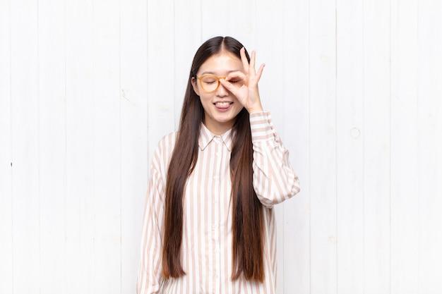 Asiatische junge frau, die glücklich mit lustigem gesicht lächelt, scherzt und durch guckloch schaut, geheimnisse ausspioniert