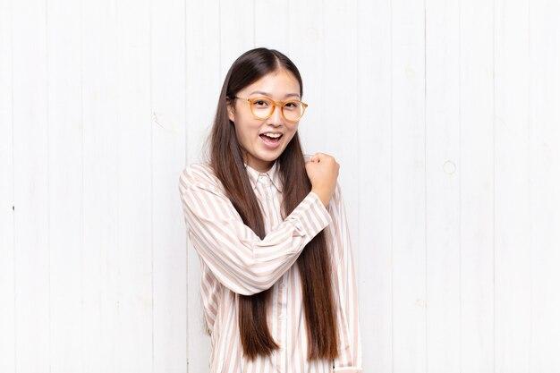 Asiatische junge frau, die glücklich, positiv und erfolgreich isoliert fühlt