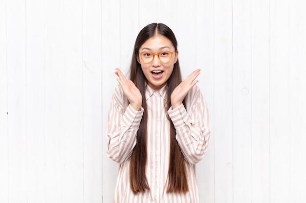 Asiatische junge frau, die glücklich und aufgeregt schaut, schockiert isoliert