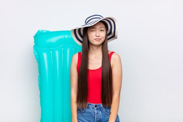 Asiatische junge frau, die glücklich und freundlich schaut, lächelt und ein auge isoliert zwinkert