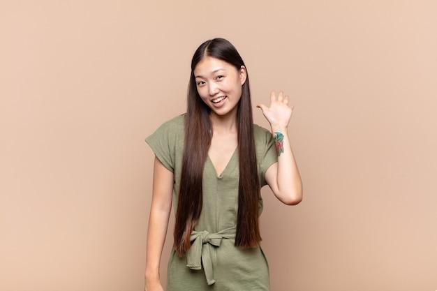Asiatische junge frau, die glücklich und fröhlich lächelt, hand winkt, sie begrüßt und begrüßt oder sich verabschiedet