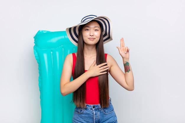 Asiatische junge frau, die glücklich, zuversichtlich und vertrauenswürdig aussieht, lächelt und siegeszeichen zeigt, mit einer positiven einstellung. sommerkonzept