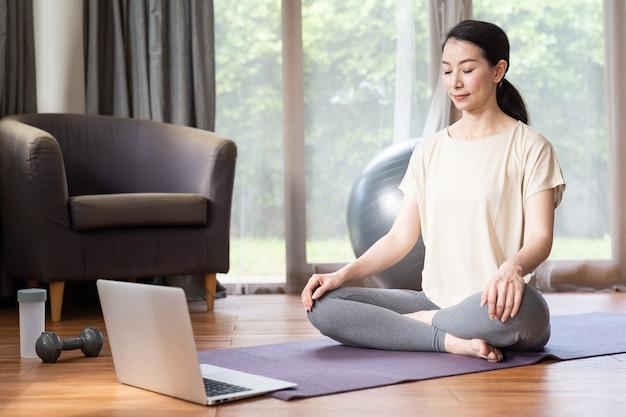 Asiatische junge frau, die heimyoga mit ihrem laptop-computer beim sitzen auf der matte praktiziert.