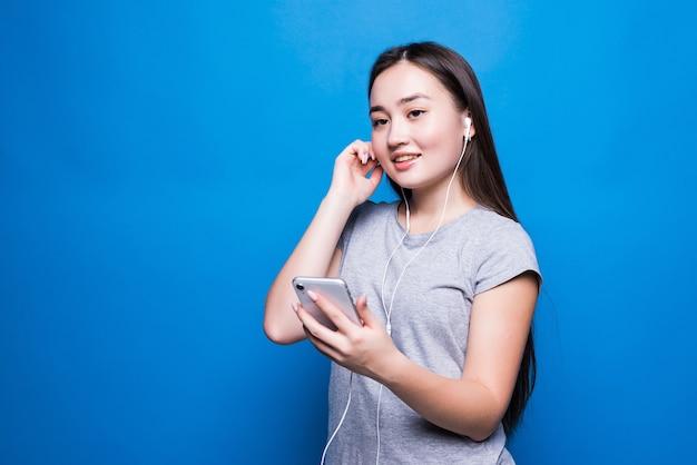 Asiatische junge frau, die hörbuch durch kopfhörer an der blauen wand hört