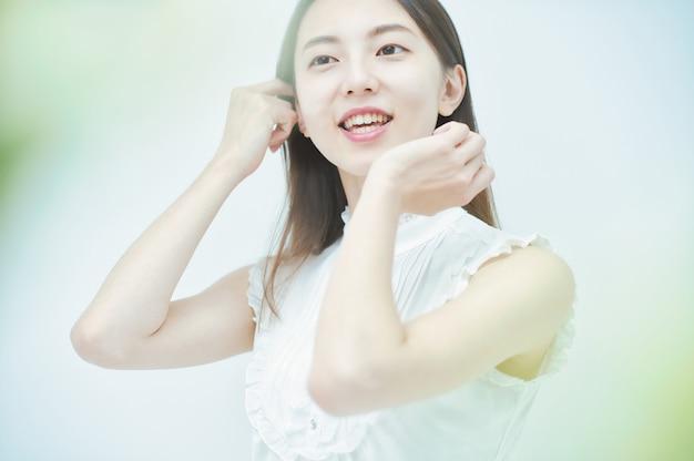 Asiatische junge frau, die ihr haar mit einem entspannten blick berührt