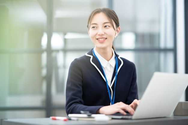 Asiatische junge frau, die im büro arbeitet