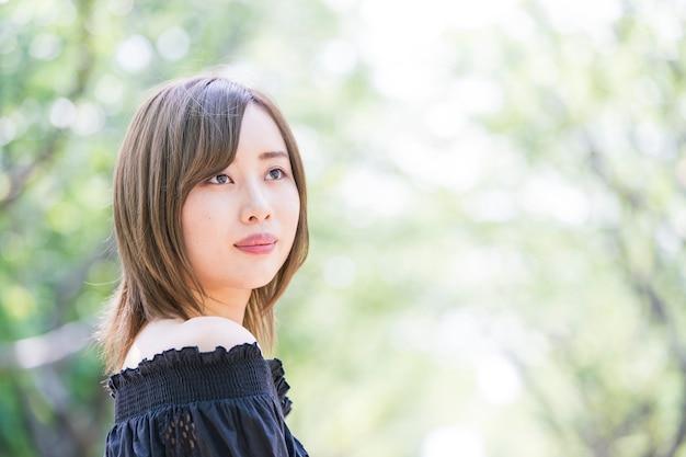 Asiatische junge frau, die im park geht
