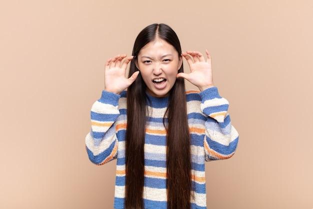 Asiatische junge frau, die in panik oder wut schreit, schockiert, verängstigt oder wütend, mit den händen neben dem kopf