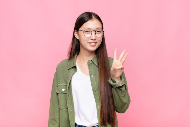 Asiatische junge frau, die lächelt und freundlich aussieht, die nummer drei oder die dritte mit der hand nach vorne zeigt und herunterzählt
