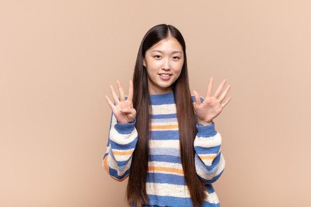 Asiatische junge frau, die lächelt und freundlich schaut, nummer neun oder neun mit hand nach vorne zeigend, countdown