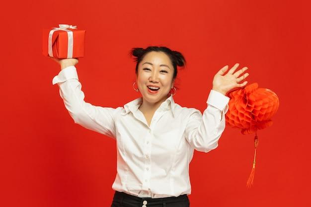 Asiatische junge frau, die laterne und geschenk auf roter wand hält