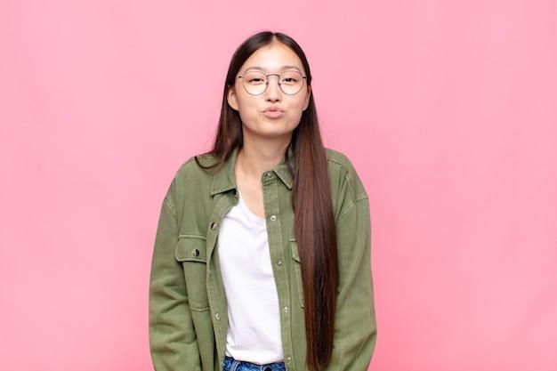 Asiatische junge frau, die lippen mit einem süßen, lustigen, glücklichen, schönen ausdruck zusammendrückt und einen kuss sendet