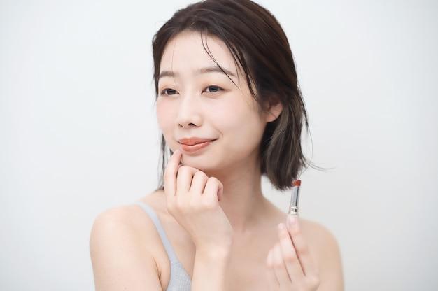 Asiatische junge frau, die lippenstift auf ihre lippen aufträgt
