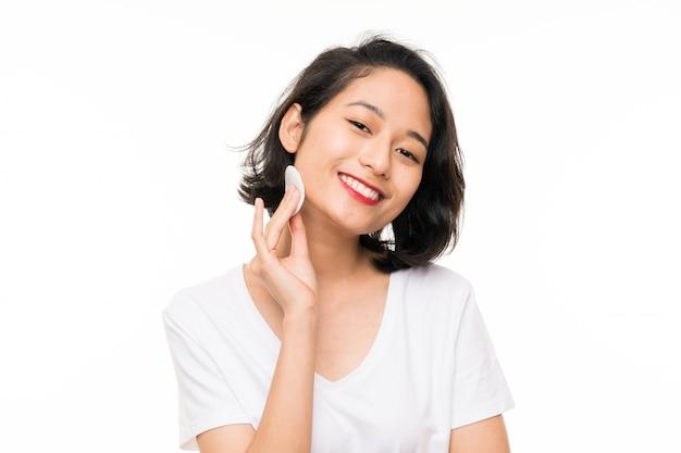 Asiatische junge frau, die make-up von ihrem gesicht mit baumwollauflage entfernt