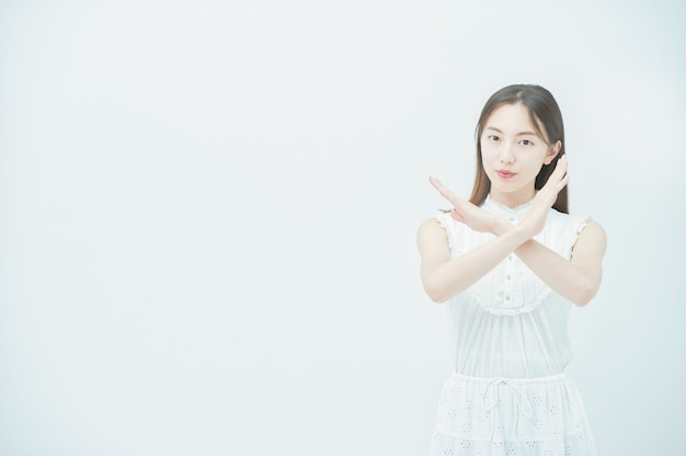 Asiatische junge frau, die mit beiden händen ein kreuzhandzeichen macht