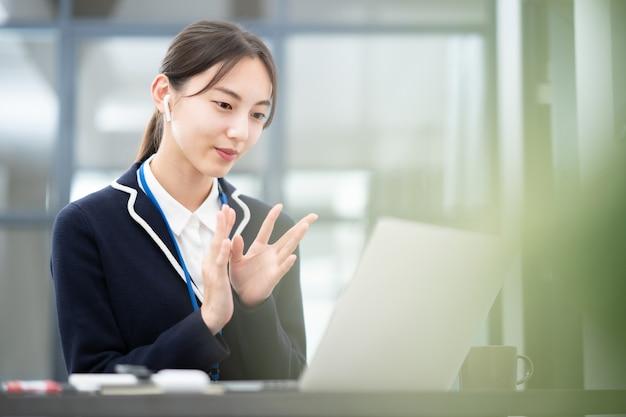 Asiatische junge frau, die mit einem computerbildschirm spricht