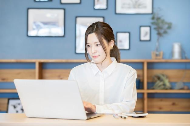 Asiatische junge frau, die mit laptop in einem lässigen raum arbeitet