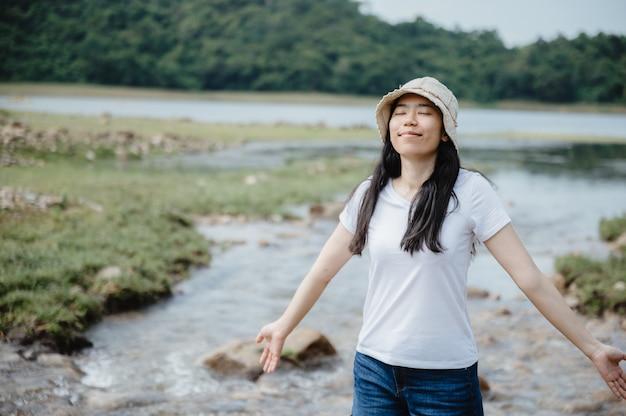 Asiatische junge frau, die mit natur, feld des wasserstroms, wasserfall im freien genießt und sich entspannt