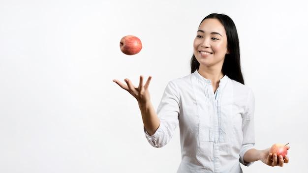 Asiatische junge frau, die mit zwei roten äpfeln jongliert