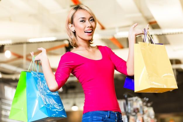 Asiatische junge frau, die mode im laden mit vielen taschen über ihren schultern einkauft