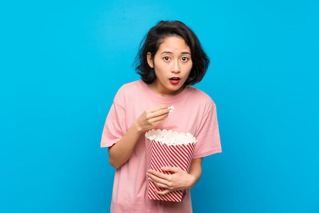 Asiatische junge frau, die popcorn isst