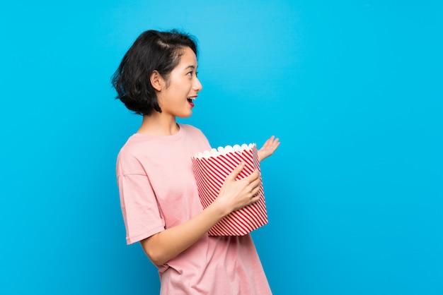 Asiatische junge frau, die popcorn mit überraschungsgesichtsausdruck isst