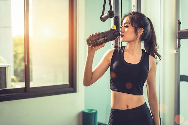 Asiatische junge frau, die protein-erschütterung oder wasser nach übungen an der eignungsturnhalle trinkt