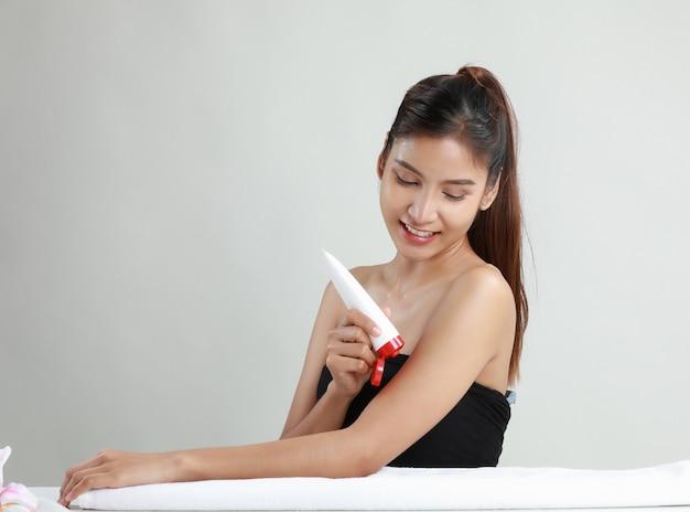 Asiatische junge frau, die rohr der feuchtigkeitscreme hält