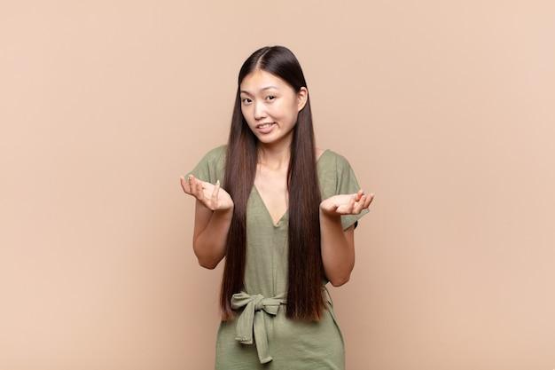 Asiatische junge frau, die sich ahnungslos und verwirrt fühlt, nicht sicher, welche wahl oder option sie wählt, wundert sich