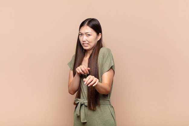 Asiatische junge frau, die sich angewidert und übel fühlt, sich von etwas bösem, stinkendem oder stinkendem zurückzieht und igitt sagt