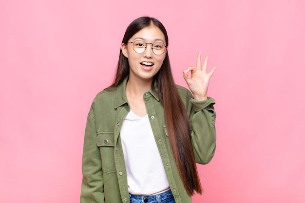 Asiatische junge frau, die sich erfolgreich und zufrieden fühlt, mit weit geöffnetem mund lächelt und mit der hand ein gutes zeichen macht