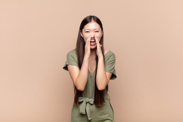 Asiatische junge frau, die sich glücklich, aufgeregt und positiv fühlt, einen großen schrei mit den händen neben dem mund gibt und ruft