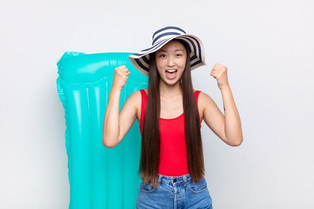 Asiatische junge frau, die sich glücklich, positiv und erfolgreich fühlt und sieg, erfolge oder viel glück feiert. sommerkonzept