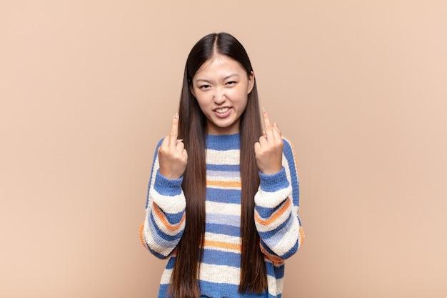 Asiatische junge frau, die sich provokativ, aggressiv und obszön fühlt
