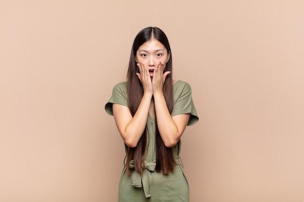 Asiatische junge frau, die sich schockiert und verängstigt fühlt und mit offenem mund und händen auf den wangen erschrocken aussieht