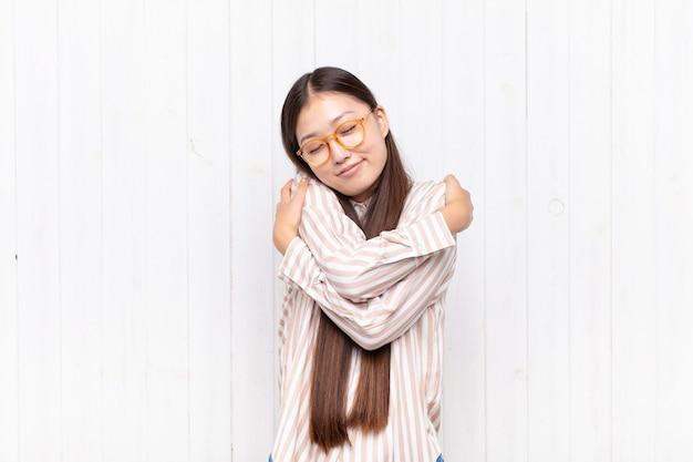 Asiatische junge frau, die sich verliebt fühlt, lächelt, kuschelt und sich selbst isoliert umarmt