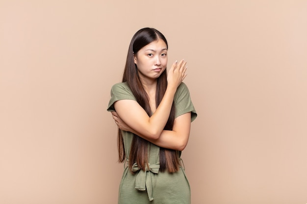 Asiatische junge frau, die sich verwirrt und ahnungslos fühlt und sich über eine zweifelhafte erklärung oder einen zweifelhaften gedanken wundert