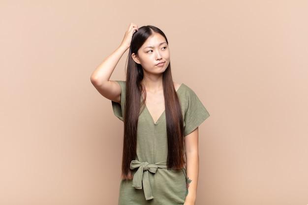 Asiatische junge frau, die sich verwirrt und verwirrt fühlt, sich am kopf kratzt und zur seite schaut