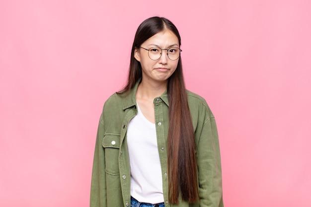 Asiatische junge frau, die sich verwirrt und zweifelhaft fühlt, sich wundert oder versucht, eine entscheidung zu treffen